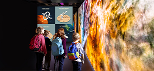 Children looking at a display of the universe at a museum,